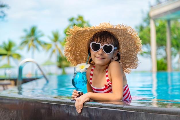 Een kind bij het zwembad drinkt een cocktail.