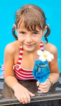 Een kind bij het zwembad drinkt een cocktail