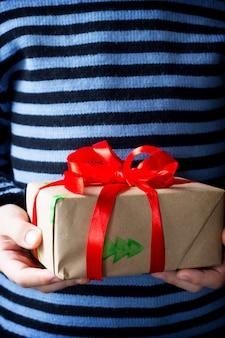 Een kind dat een kerst geeft, presenteert een doos met een rood lint