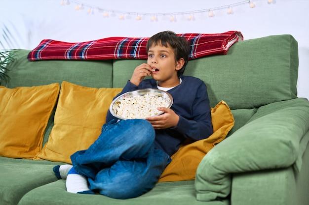 Een kind dat op de bank tv kijkt en thuis popcorn eet