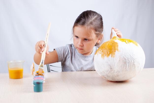 Een kind doopt een penseel in verf om een zelfgemaakte pompoen te versieren voor halloween, een hobby voor zelfisolatie