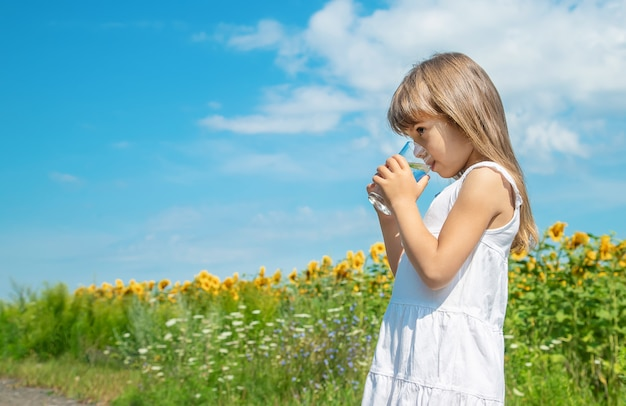 Een kind drinkt water op de achtergrond van het veld