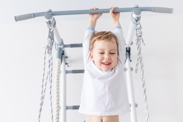 Een kind een jongen doet sporten of oefeningen op de zweedse muur van het huis.
