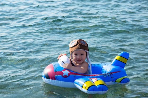 Een kind, een jongen met een pilotenhelm en een opblaasbare kinderring zwemt in de zee