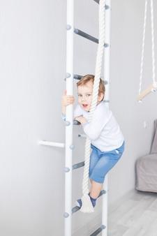 Een kind een jongen sport of oefeningen doet op de zweedse muur van het huis
