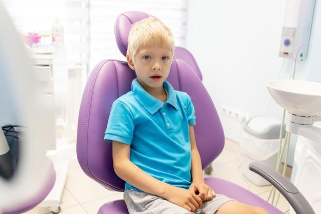 Een kind een jongen van vijf jaar zit in een lila stoel in een tandartspraktijk