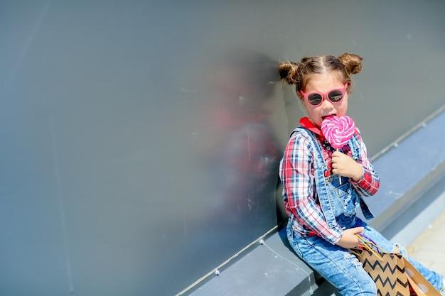 Een kind een meisje met een lollipop in haar handen zit op straat in een denim jumpsuit en zonnebril