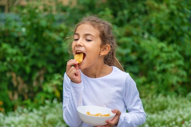 Een kind eet chips op straat. selectieve aandacht.