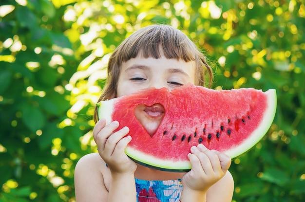 Een kind eet watermeloen. selectieve aandacht. voedsel