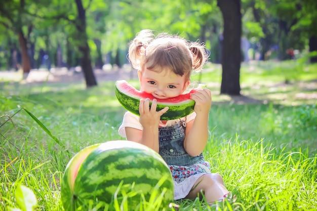 Een kind eet watermeloen. selectieve aandacht.