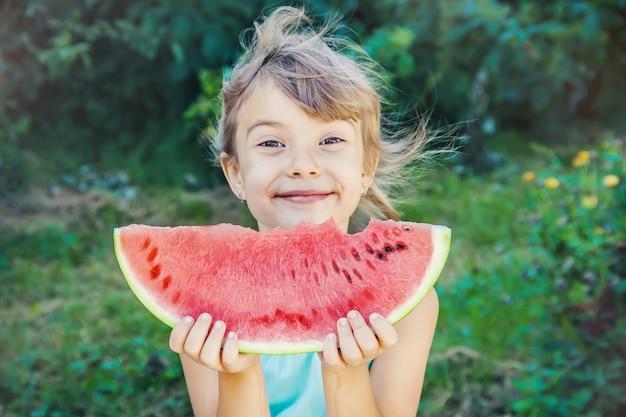 Een kind eet watermeloen.