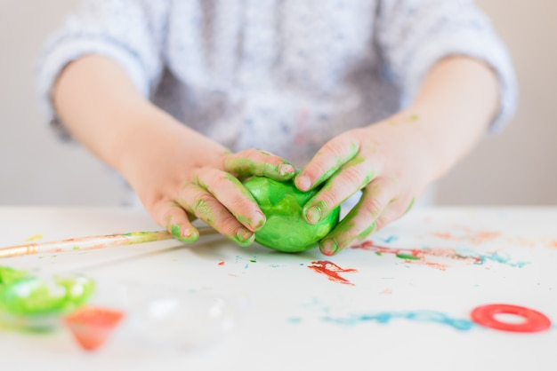 Een kind heeft een groen paasei in zijn handen gekleurd met verf op een witte tafel.