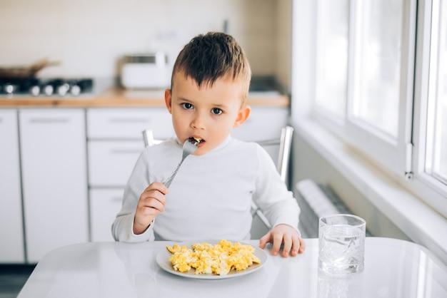 Een kind in de namiddag op een wit-lichte keuken in een witte trui eet een omelet
