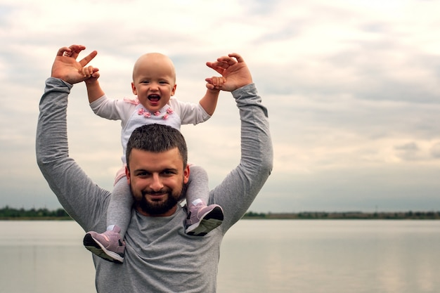 Een kind in de nek van zijn vader. loop langs het water. baby en papa tegen de hemel.