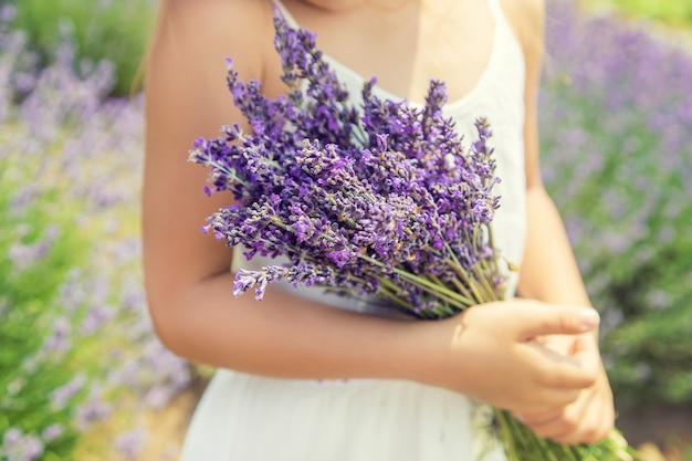 Een kind in een bloeiend veld met lavendel.
