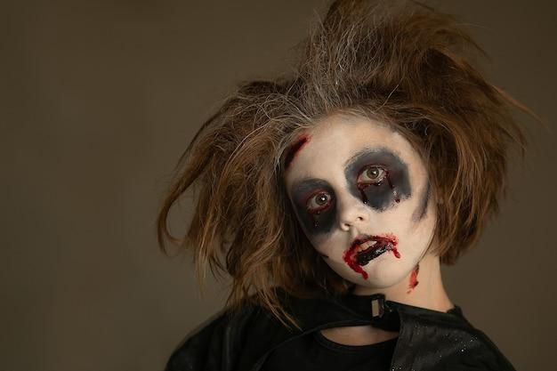 Een kind in een carnavalskostuum met een enge schminken op halloween
