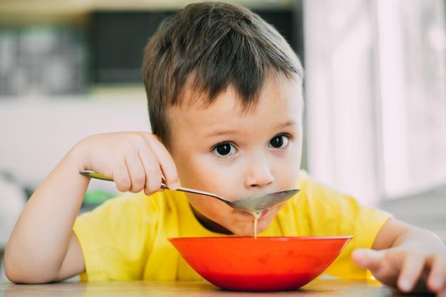 Een kind in een geel t-shirt in de keuken dat een nationaal russisch gerecht eet dat okroshka heet