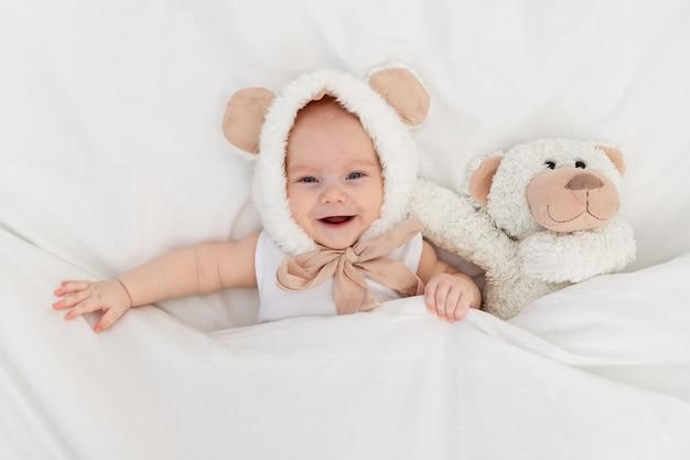 Een kind in een grappige hoed met oren met een teddybeer onder de deken. textiel en beddengoed voor kinderen. een pasgeboren baby is wakker geworden of gaat naar bed