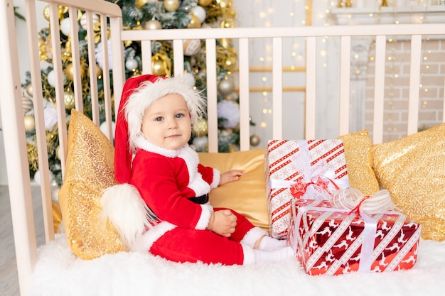 Een kind in een kerstman kostuum met een cadeau bij de kerstboom met een gouden decor zit thuis in een wieg
