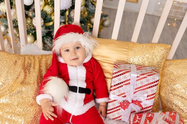 Een kind in een kerstman kostuum met een cadeau bij de kerstboom met een gouden decor