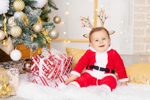 Een kind in een kerstman kostuum zit bij de kerstboom met geschenken, het concept van nieuwjaar en kerstmis