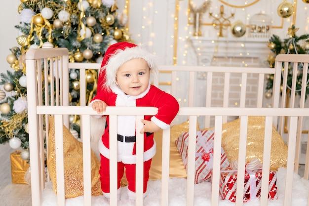 Een kind in een kerstmankostuum staat thuis in een wieg bij een kerstboom met een gouden decor