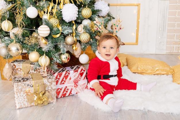 Een kind in een kerstmankostuum zit bij de kerstboom met cadeaus, het concept van nieuwjaar en kerstmis