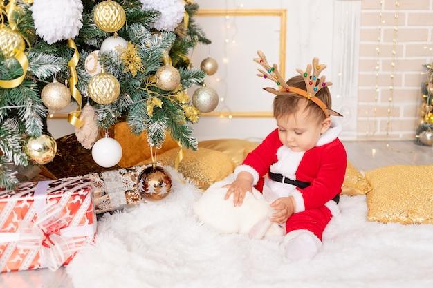 Een kind in een kerstmankostuum zit bij de kerstboom met een konijn, het concept van nieuwjaar en kerstmis