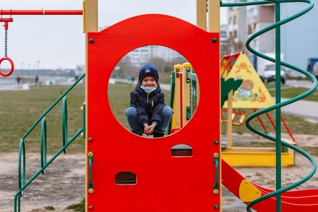 Een kind in een medisch masker dat op een speelplaats speelt