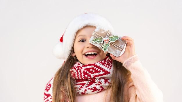 Een kind in een nieuwjaarsoutfit houdt een feestelijke geschenkdoos vast.