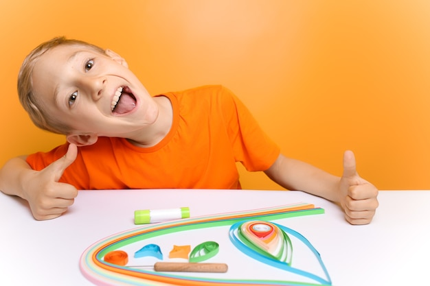 Een kind in een oranje t-shirt lacht naar de camera voordat hij dunne papieren stroken draait in de quilling-techniek