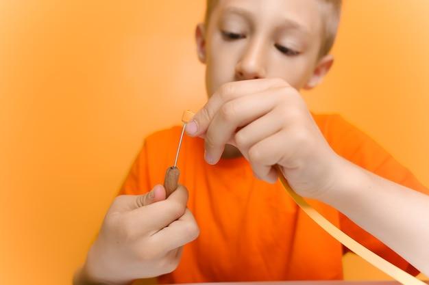 Een kind in een oranje t-shirt probeert een dunne strook papier in een quillingtool te steken