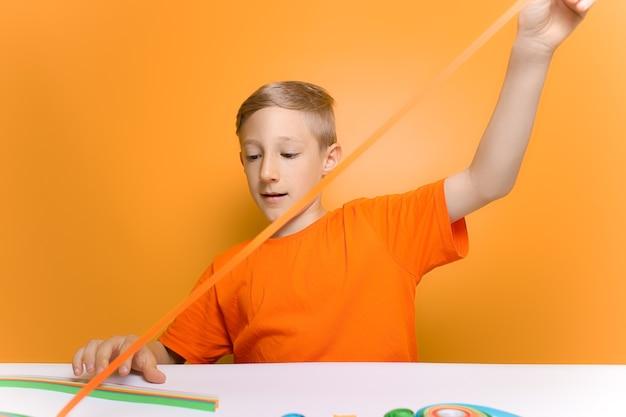 Een kind in een oranje t-shirt spant een dunne strook papier voor zich uit om te quilling