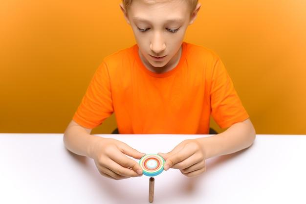Een kind in een oranje t-shirt zit aan een tafel en kijkt naar het draaien van flinterdunne stroken. maakt blanco's voor zelfgemaakte ansichtkaarten