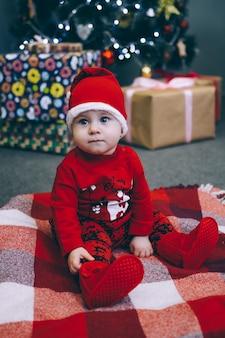 Een kind in een pak van de kerstman zit onder een kerstboom