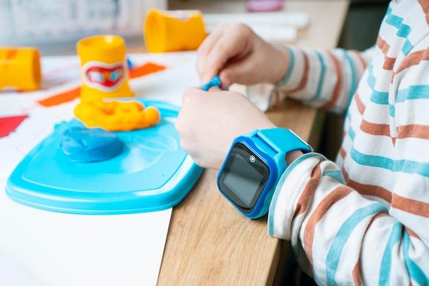 Een kind in een slim horloge beeldhouwt uit plasticine in een kleuterschool.