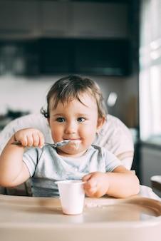 Een kind in een t-shirt in de keuken die een omelet met worst en tomaten eet met een vork