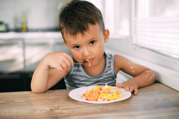 Een kind in een t-shirt in de keuken eet een omelet met worst en tomaten met een vork