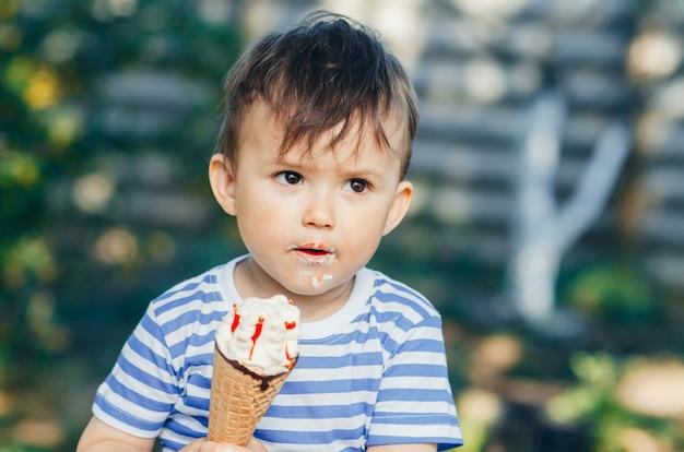 Een kind in een t-shirt op een bankje dat ijs eet in de zomer erg warm en lekker