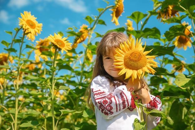 Een kind in een veld met zonnebloemen in een geborduurd shirt.