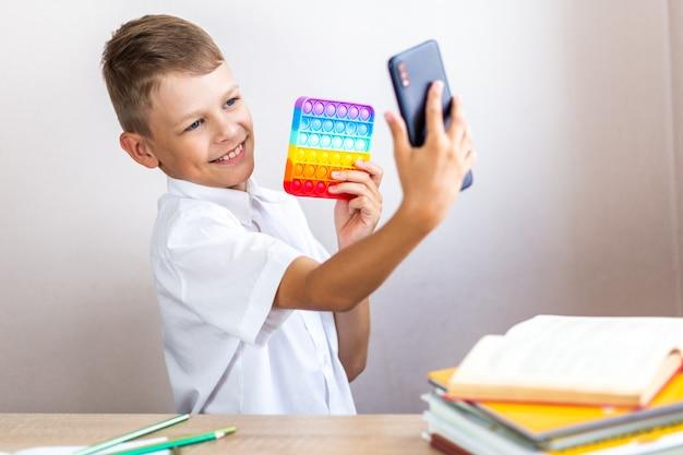 Een kind in een wit overhemd zit aan een tafel en maakt een selfie met een antistress speelgoed