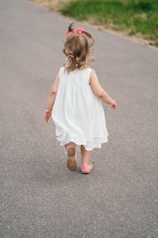 Een kind in een witte jurk rent over het pad