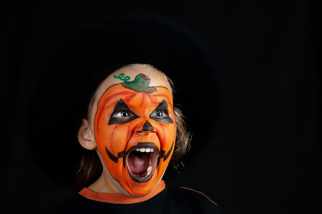 Een kind in een zwarte hoed en pompoenmake-up schreeuwt, geïsoleerd.