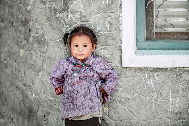 Een kind in het pokhara-gebied staat in de zon. in het koude weer voor warmte van het lichaam, pokhara, nepal