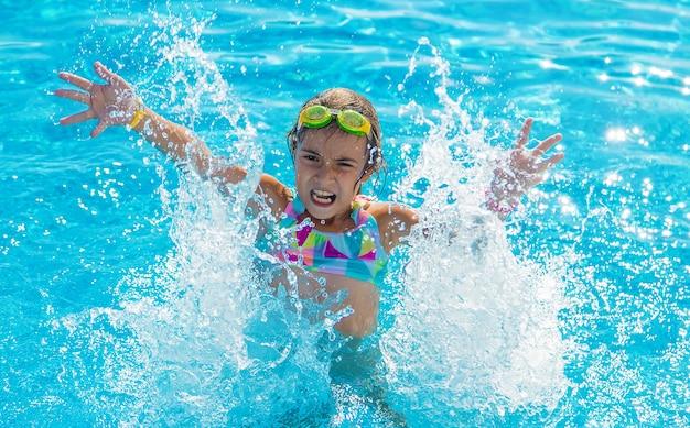 Een kind in het zwembad spettert water. selectieve aandacht.