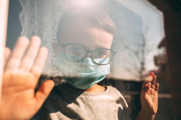 Een kind in quarantaine vanwege een virus zit thuis in een masker en kijkt uit het raam op een zonnige dag. coronavirus en luchtvervuiling pm2.5 concept. covid-19