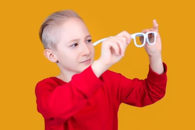 Een kind in rode kleren onderzoekt een bril op een gele achtergrond