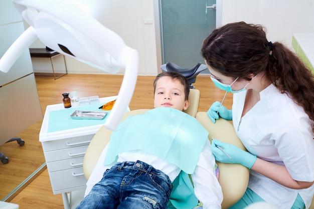 Een kind jongen en tandarts vrouw in tandheelkundige kliniek