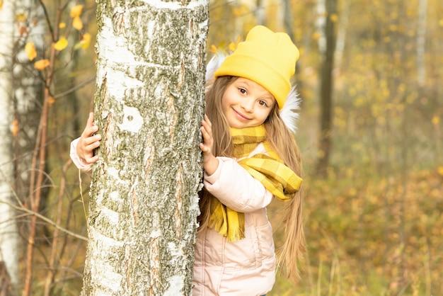 Een kind kijkt uit achter een berk in de herfst.