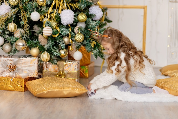 Een kind legt thuis een brief voor de kerstman onder een kerstboom met een gouden decor
